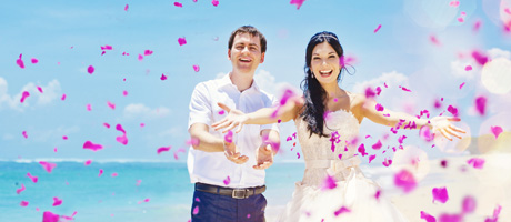 Bride and groom toss petals on beach