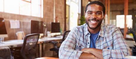 Hombre sonriente en escritorio de aula