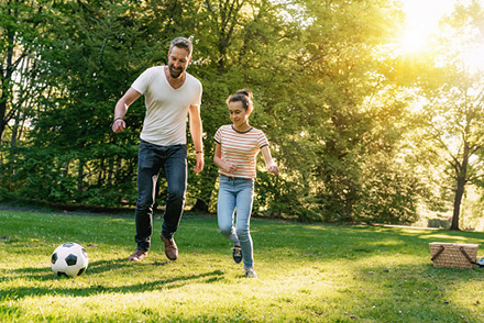 Dad and daughter playing soccer at a park