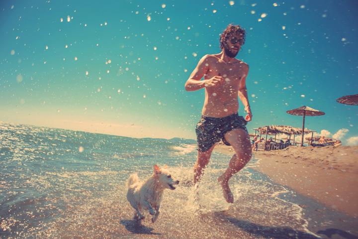 un hombre con su perro corren en la playa