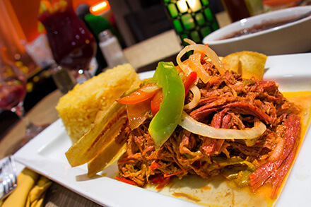 Plate of ropa vieja with rice and plantain chips