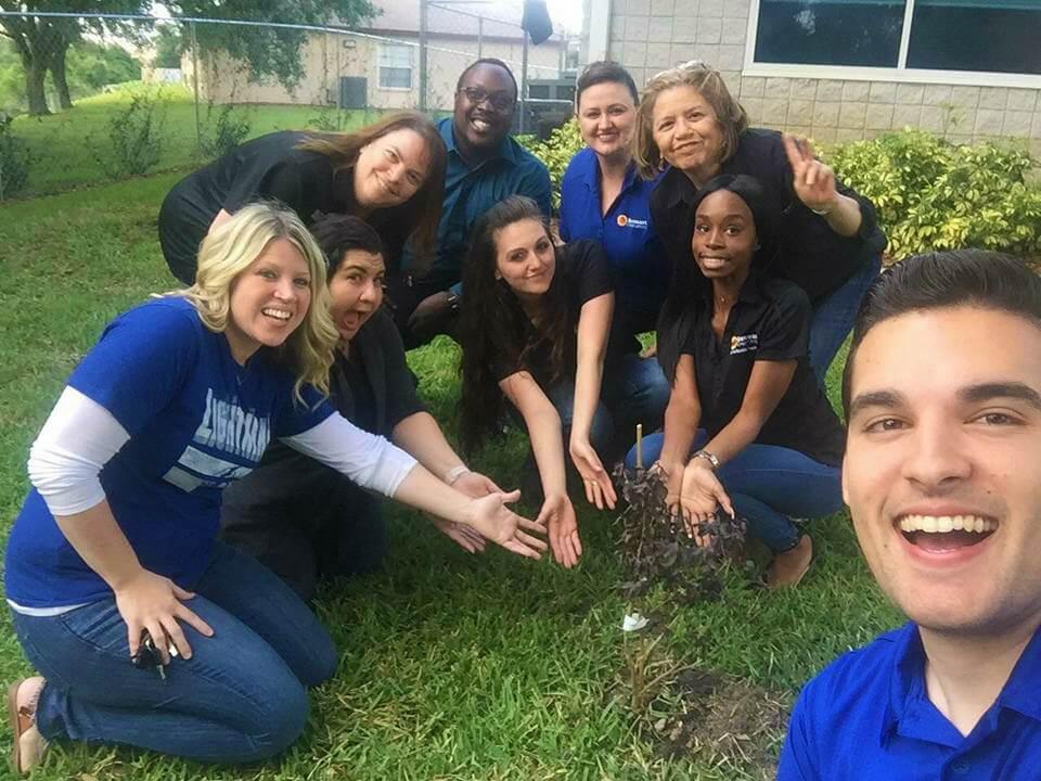 Los empleados deSuncoast Credit Unionmuestran un árbol recién plantado en el Día de la Tierra