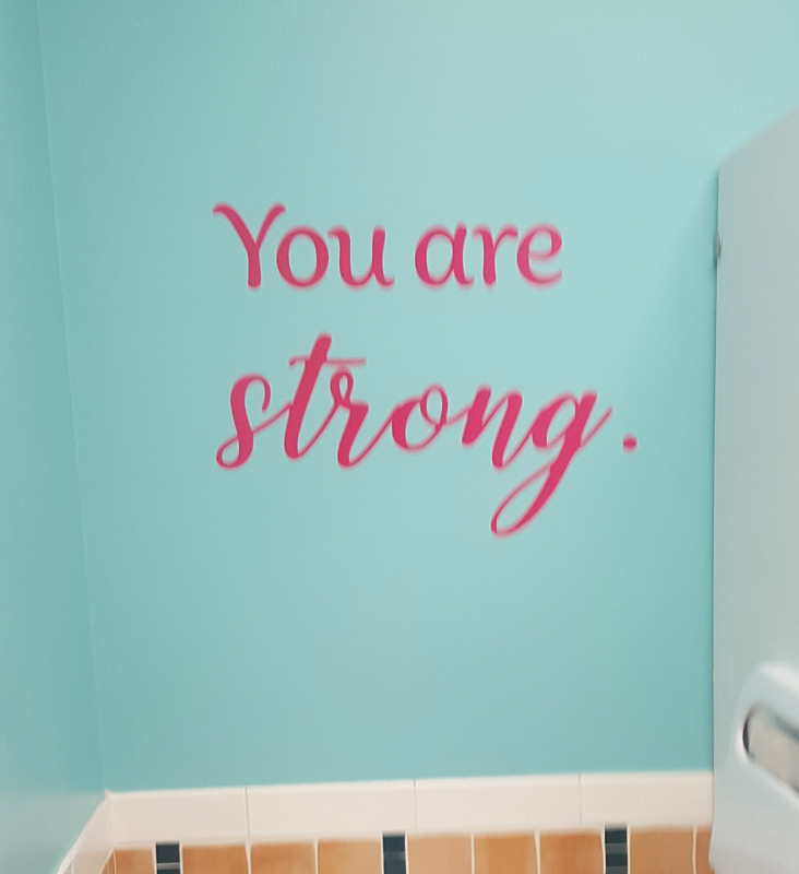 La calcomanía para pared en el Centro para niñas dice You are strong (Eres fuerte)