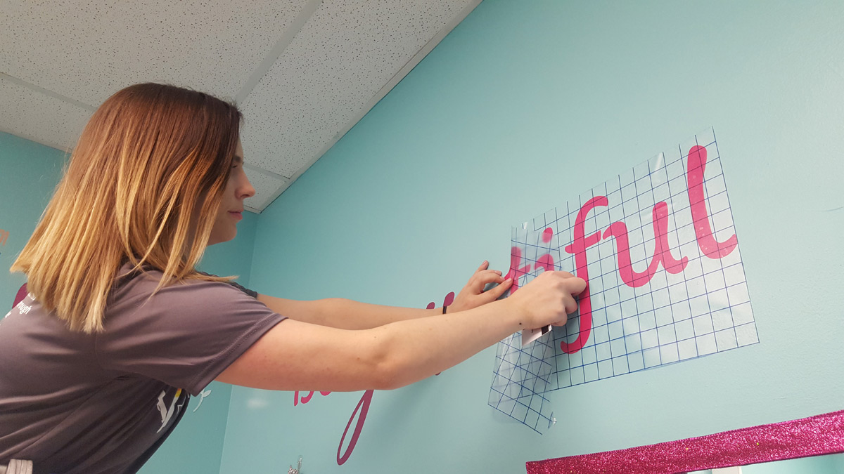Suncoast Credit Union staff affixes wall decal in girls bathroom at Centre for Girls