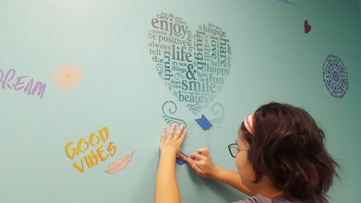 El personal de Suncoast Credit Union pinta a mano decoraciones en el baño de niñas del Centre for Girls