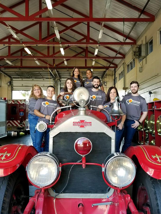 El personal de Suncoast Credit Union junto a un camión de bomberos antiguo en una estación de bomberos en Plant City