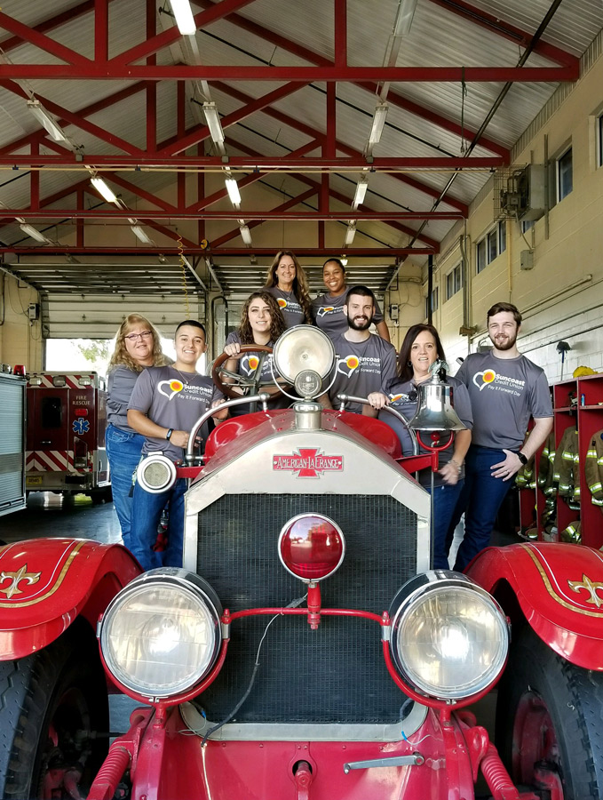 Suncoast Credit Union staff by a vintage firetruck in a firehouse in Plant City