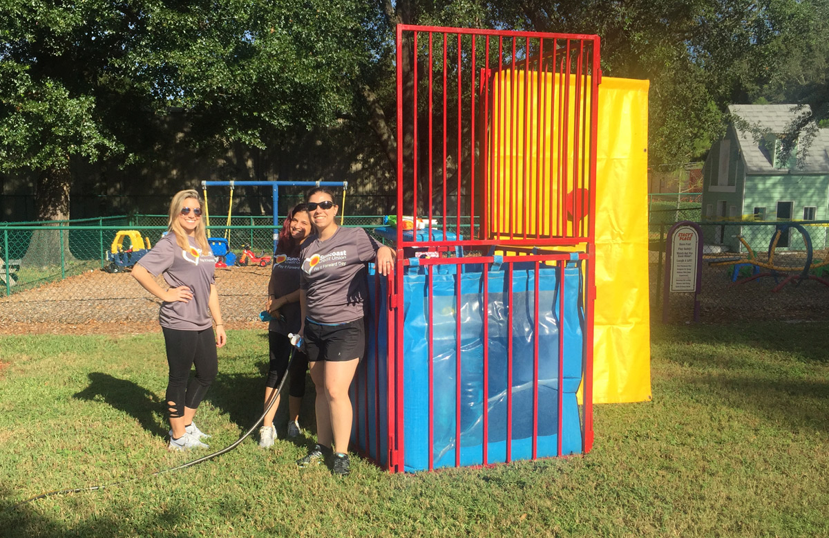 Suncoast Credit Union sets up a dunk tank while volunteering at the Kid's Place