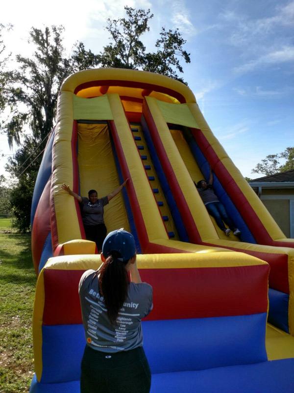Miembros del personal de Suncoast Credit Union se deslizan por un tobogán inflable gigante en Kid's Place