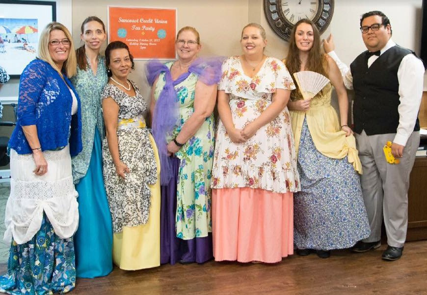Suncoast Credit Union staff dressed up in Victorian dresses while volunteering at a Tea Party for Royal Palms Retirement Home
