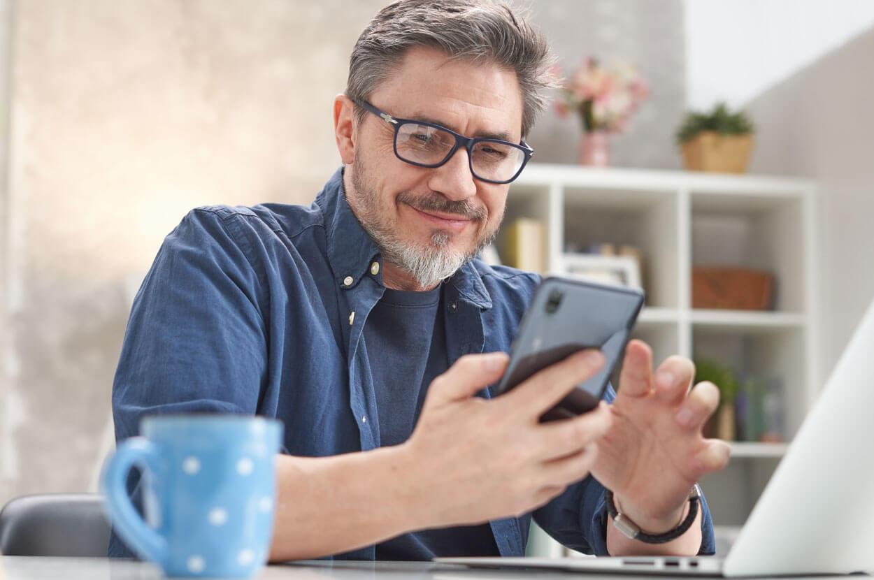 Hombre sentado en el escritorio usando su teléfono