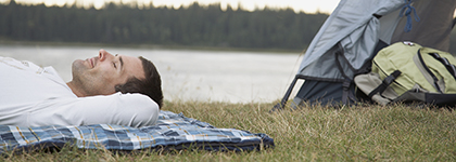 A restful looking man lays out by his camping equipment near a lake