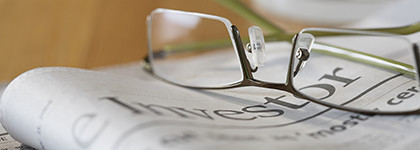A pair of glasses rest upon an investment newspaper