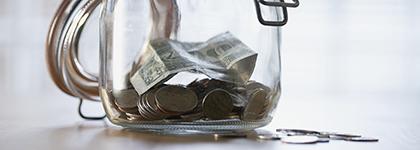 Un frasco de ahorros con monedas y billetes de poco valor