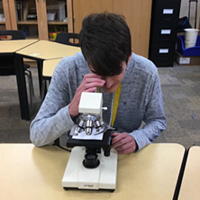 student looks into microscope in glades county