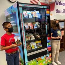 Dos niños junto a una máquina expendedora de libros