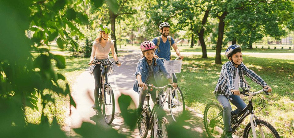 Una familia pasea en bicicleta por el parque