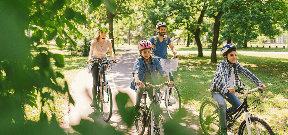 A happy family rides through the park on their bikes
