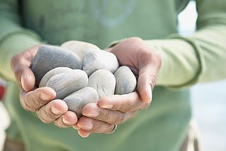 someone holding small pebble rocks in both hands