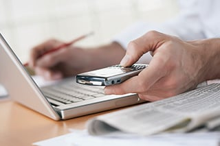 hombre frente a una laptop, con un teléfono celular en una mano