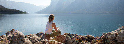 woman sitting on rocks looking out into lake and mountains