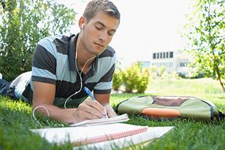 estudiante haciendo sus deberes sobre la grama con auriculares puestos