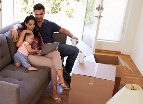 New homeowners sit in their living room