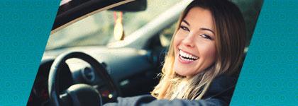 Mujer en el asiento del conductor de un automóvil sonriendo a la cámara