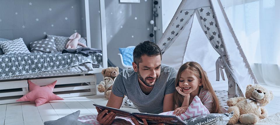 Padre e hija leyendo un libro en el piso del dormitorio