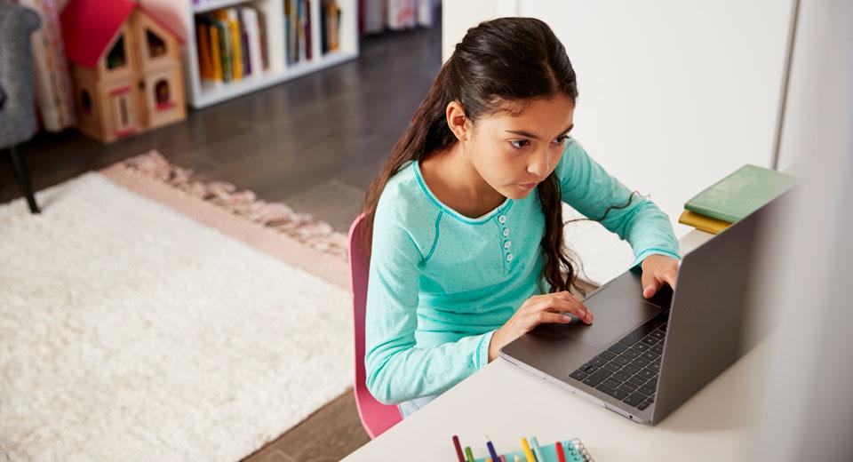 Niña estudiando es su casa con un laptop
