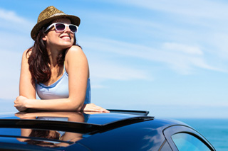 Woman in hat and sunglasses enjoys a sunny day from the sunroof of her car