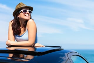 Una mujer con sombrero y lentes de sol disfrutando de un día soleado desde el techo corredizo de su auto