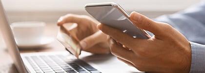 Primer plano de las manos de una persona sosteniendo un teléfono y una tarjeta de crédito cerca de su laptop