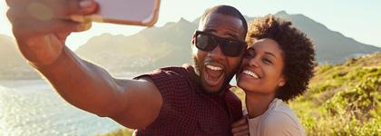 una pareja se toma una autofoto en la cima de una montaña